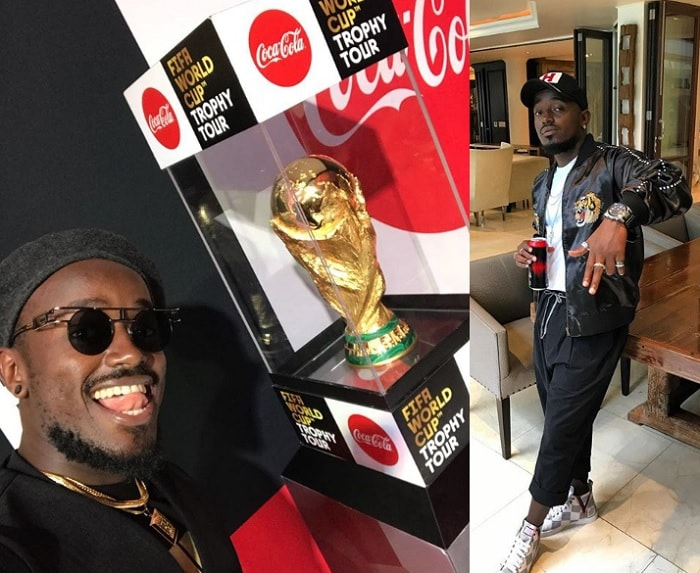 Ykee Benda strikes a pose next to the FIFA World Cup Trophy during the time it was in Kampala