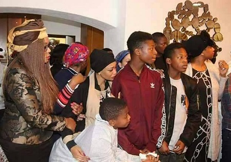 Zari and her three sons looking at the casket with Ivan Semwanga's body